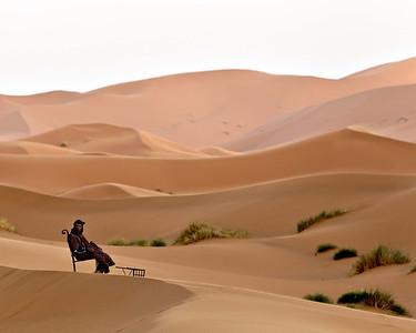 A berber sits comfortably in the desert sun despite his dark attire